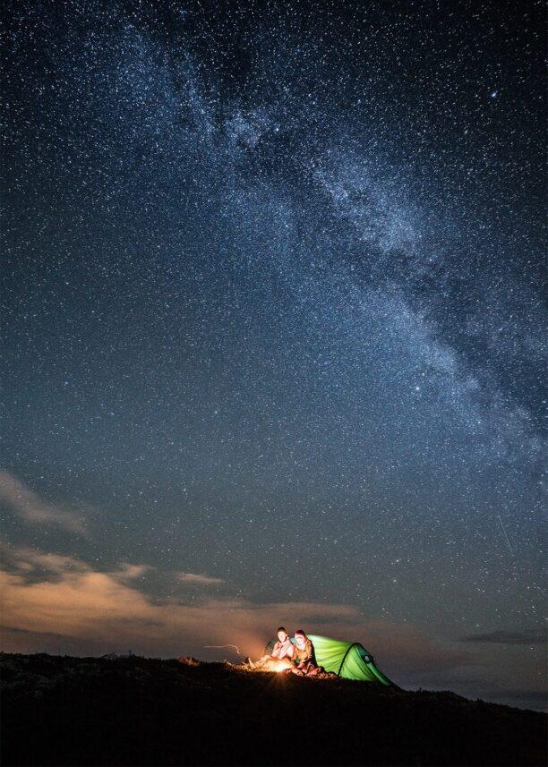 To tettere varmer seg på et bål under stjernehimlen, fotokunst veggbilde / plakat av Bård Basberg