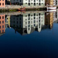 Bygninger som speiler seg i vannet., fotokunst veggbilde / plakat av Eirik Sørstrømmen