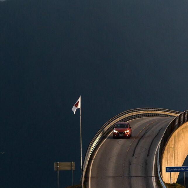 Bil kjører over bru i solnedgang, fotokunst veggbilde / plakat av Kristoffer Vangen