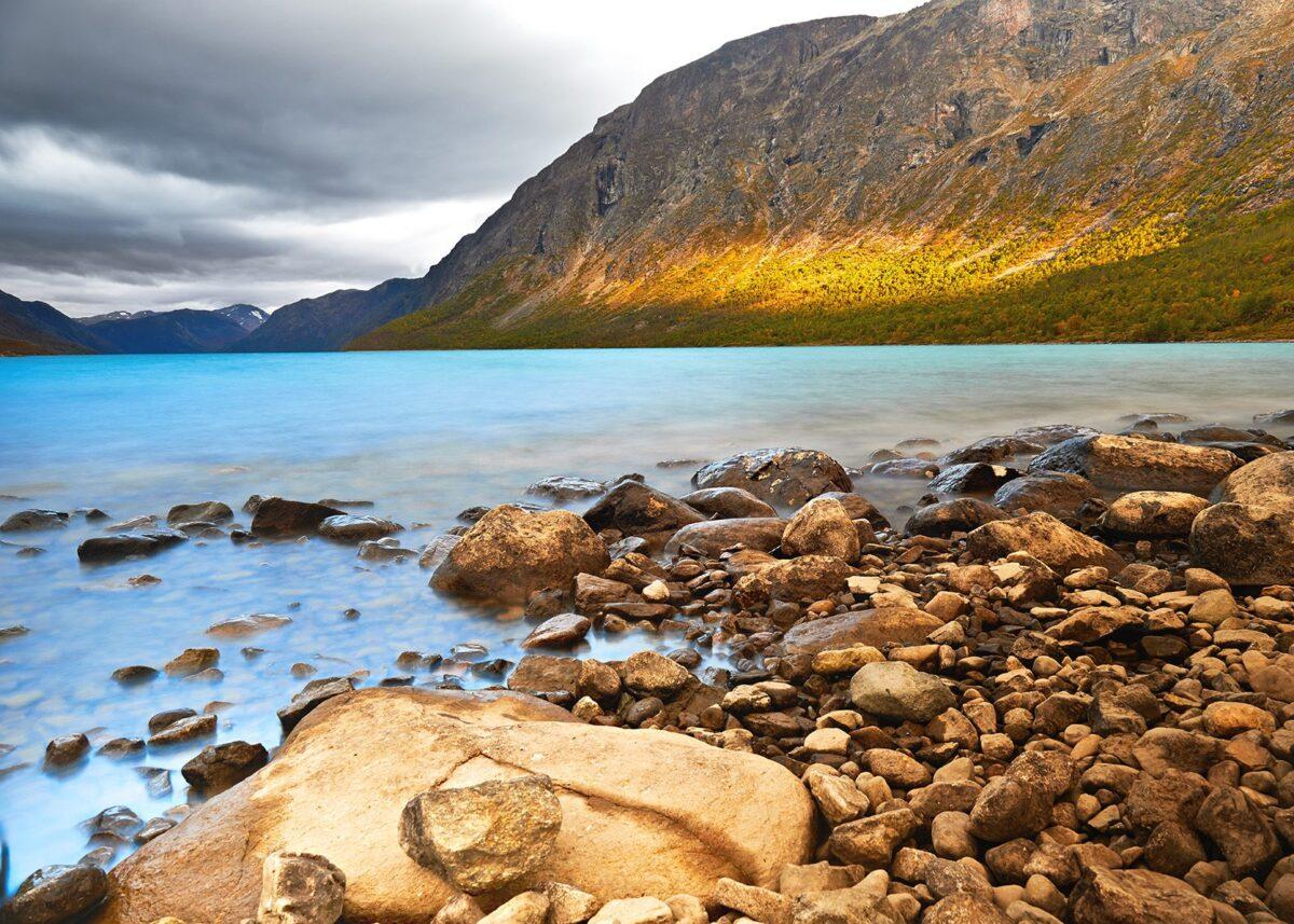 Stille vann mot stein og morgensol i fjellsiden av Peder Aaserud Eikeland