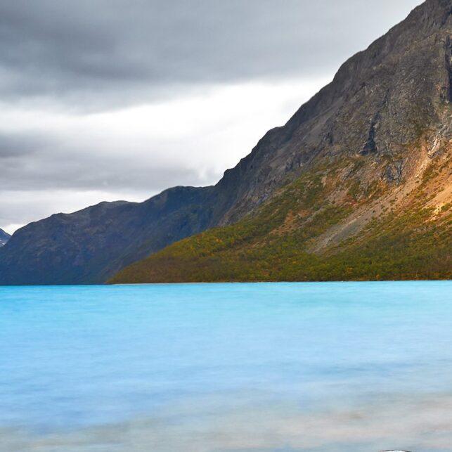 Stille vann mot stein og morgensol i fjellsiden, fotokunst veggbilde / plakat av Peder Aaserud Eikeland