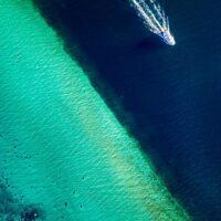 En båt på tur langs strandlinjen, fotokunst veggbilde / plakat av Sindre Krane Olsen