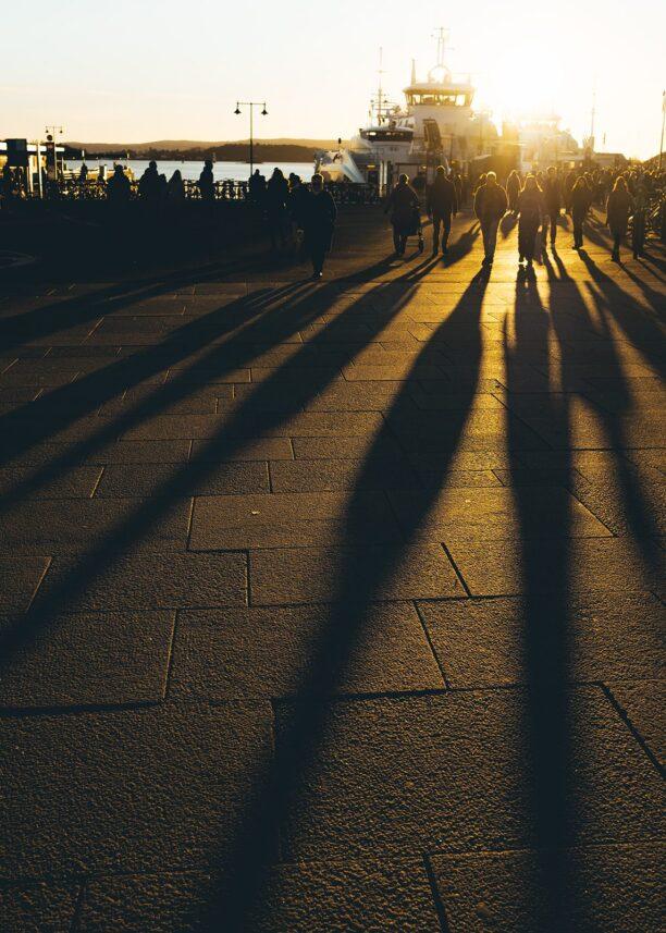 Mennesker som kaster lange skygger i solnedgangen, fotokunst veggbilde / plakat av Tor Arne Hotvedt