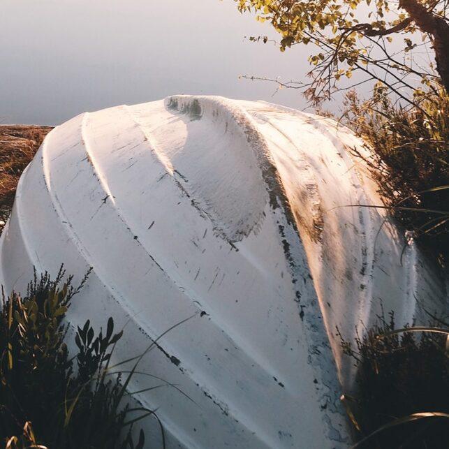 Stille vann med robåt på land i forgrunnen, fotokunst veggbilde / plakat av Tor Arne Hotvedt