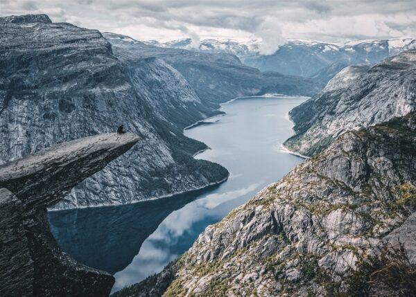 Person sitter på tuppen av Trolltunga, fotokunst veggbilde / plakat av Tor Arne Hotvedt