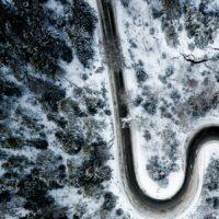 Et dronebilde ovenfra som viser kontrast mellom snø og vei, fotokunst veggbilde / plakat av Tor Arne Hotvedt