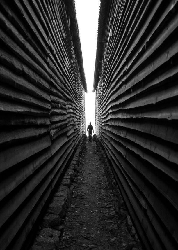 Person går mellom bygningene på Fredriksvern verft i Stavern, fotokunst veggbilde / plakat av Tor Arne Hotvedt