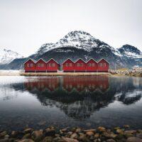 Sju røde naust i Sunndalsøra speiler seg i vannet, fotokunst veggbilde / plakat av Tor Arne Hotvedt