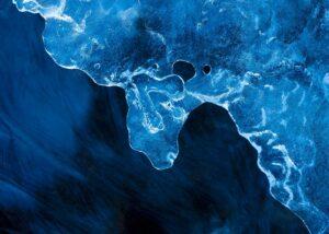 Beveren speiler seg i stille vann mens den passerer, fotokunst veggbilde / plakat av Kjell Erik Moseid