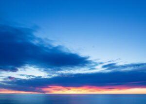En lav sol er i ferd med å klatre opp på himmelen. Den henger lavt, like over de mange bruene over elven Seinen i Paris, Frankrike. , fotokunst veggbilde / plakat av Marit Bye Gjermshus